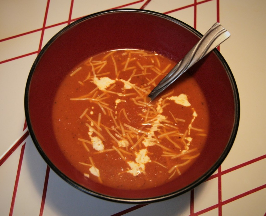 Fresh tomato soup in a bowl garnished with Parmesan cheese and heavy cream