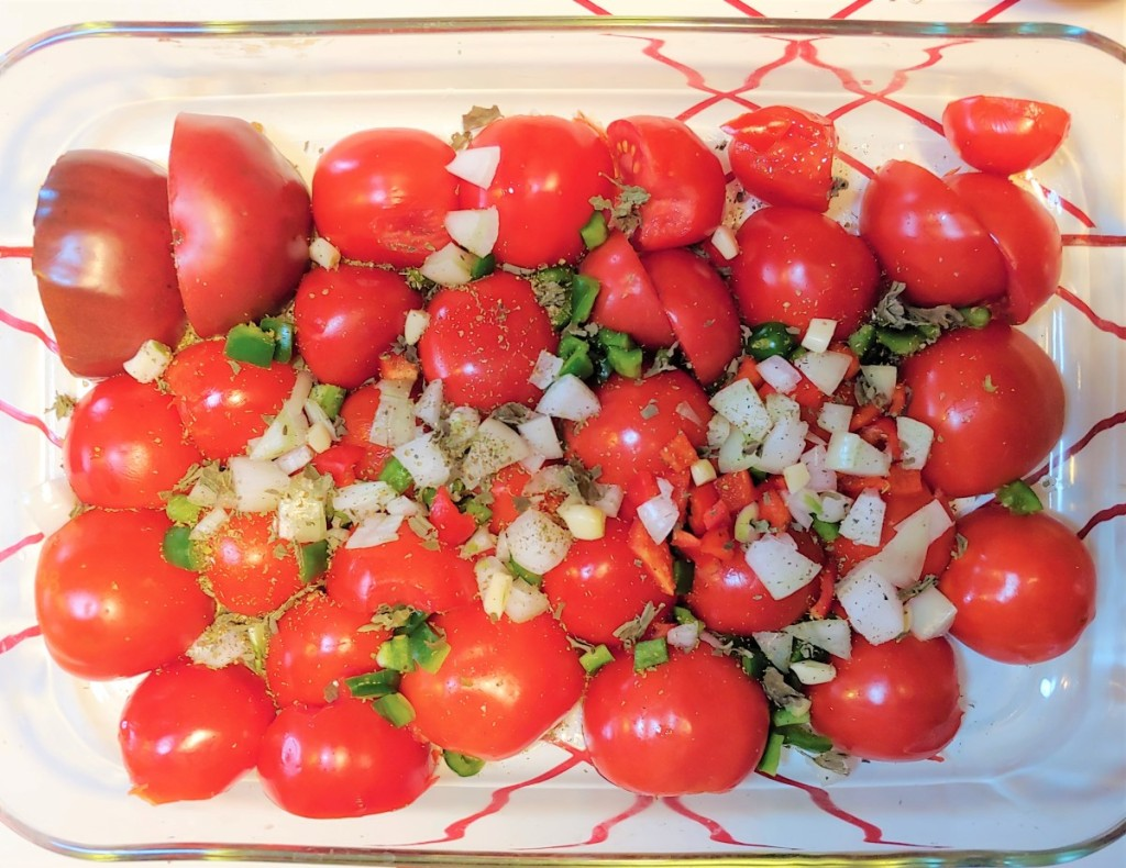 Fresh tomatoes, peppers, onions, garlic, and spices ready in a pan for roasting.