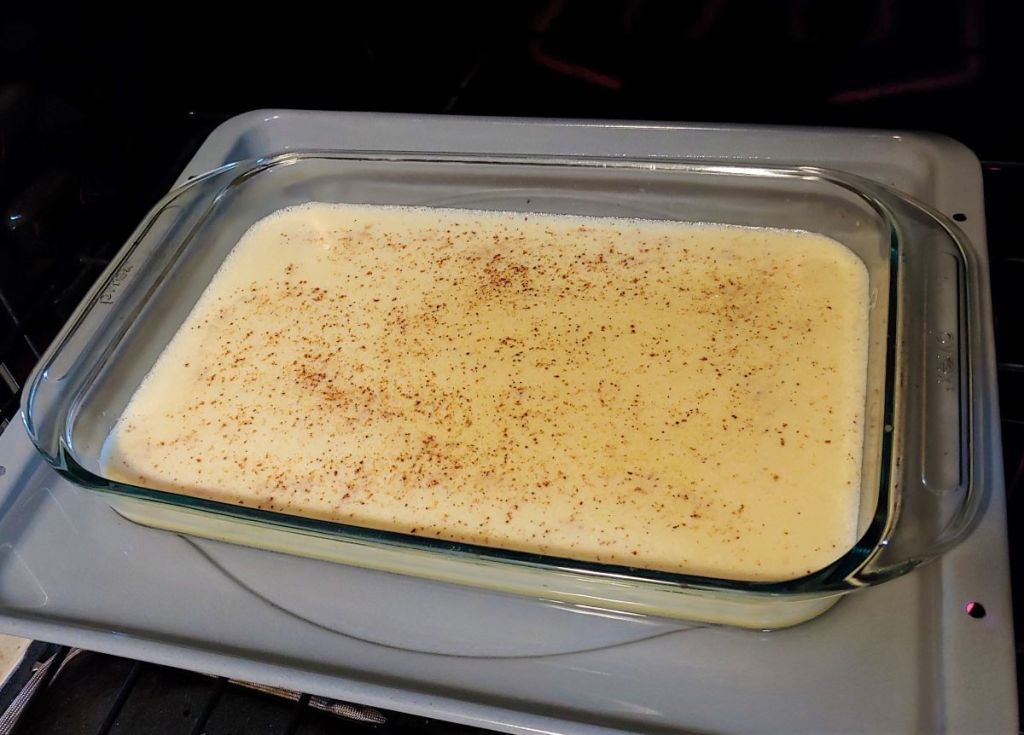Egg custard in a baking dish going into the oven inside a roasting pan filled with water