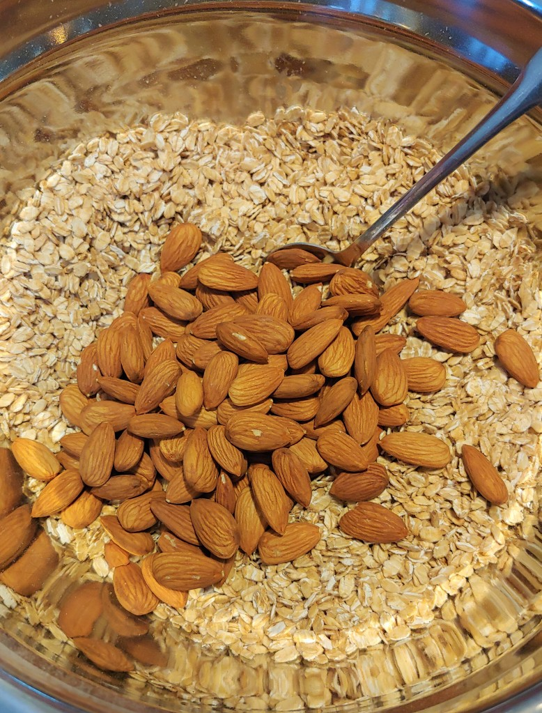 Rolled oats and whole almonds in a metal bowl